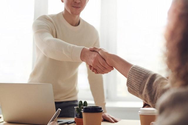 podávání ruky, muž ve světlém svetru podává ruku přes stůl ženě