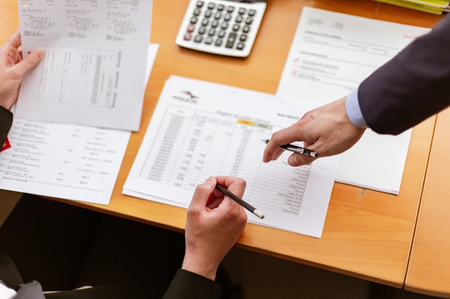 stůl, papíry, kalkulačka a ruce v obleku drží propisky